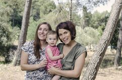 Portrait of happy lesbians mothers with a baby.  Homosexual fami. Ly in a countryside Stock Image