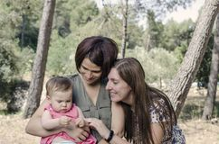 Portrait of happy lesbians mothers with a baby.  Homosexual fami. Ly in a countryside Stock Photos