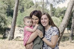 Portrait of happy lesbians mothers with a baby.  Homosexual fami. Ly in a countryside Royalty Free Stock Images