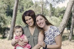 Portrait of happy lesbians mothers with a baby.  Homosexual fami. Ly in a countryside Royalty Free Stock Photos