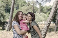 Portrait of happy lesbians mothers with a baby.  Homosexual fami. Ly in a countryside Royalty Free Stock Image
