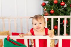 Portrait of a happy little baby six months in a crib at home by the Christmas tree, new year and holiday concept