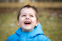 Portrait of a happy little boy. Portrait of a cute little brown-haired boy with a happy, joyful expression on his face.  He is wearing a blue coat and is playing Royalty Free Stock Photos