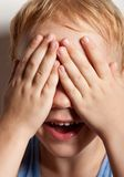 Portrait of happy little boy covering his eyes stock photo