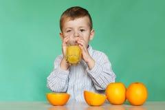 Portrait of happy little boy drinking orange juice. stock photos