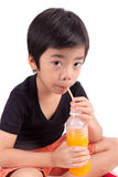 Portrait of happy little boy drinking orange juice Royalty Free Stock Photo