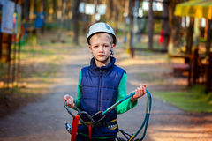 Portrait of happy little boy having fun in adventure park smiling to camera wearing helmet and safety equipment. Stock Photos