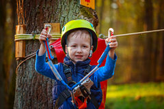 Portrait of happy little boy having fun in adventure park smiling to camera wearing helmet and safety equipment. Royalty Free Stock Images