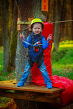 Portrait of happy little boy having fun in adventure park smiling to camera wearing helmet and safety equipment. Royalty Free Stock Image