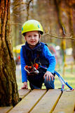 Portrait of happy little boy having fun in adventure park smiling to camera wearing helmet and safety equipment. Stock Photo