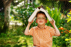 Portrait Happy little boy holding a big book on his first day to school or nursery. Outdoors, Back to school concept. Stock Image