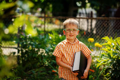 Portrait Happy little boy holding a big book on his first day to school or nursery. Outdoors, Back to school concept Stock Images