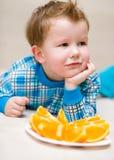 Portrait of a happy little boy. With orange Stock Photo
