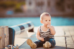 Portrait of happy little boy playing outdoors at dock near the sea Stock Image