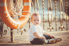Portrait of happy little boy playing outdoors at dock near the sea Stock Photos