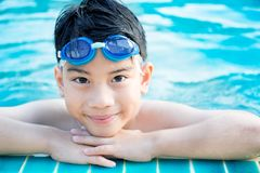 Portrait of happy little boy playing in the pool Stock Photos