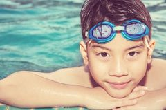 Portrait of happy little boy playing in the pool Stock Image