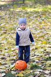 Happy little boy in cap and vest is standing with halloween pumpkin surrounded by fallen leaves. Portrait of little two years old boy in cap and vest standing stock photo