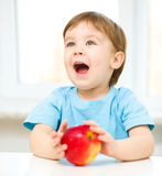 Portrait of a happy little boy with apple stock images