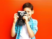 Portrait happy little boy teenager with retro camera on red stock photos