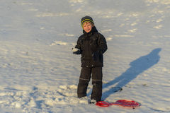 Portrait Happy little boy winter clothing having fun in fresh white winter snow in evening light Stock Photos