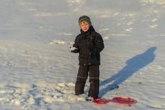 Portrait Happy little boy winter clothing having fun in fresh white winter snow in evening light Stock Photos