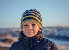 Portrait Happy little boy winter clothing having fun in fresh white winter snow in evening light Royalty Free Stock Image