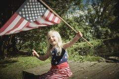 Positive little girl waving American flag Royalty Free Stock Photo