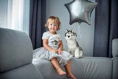 Portrait of happy little child with curly blonde hair in casual clothes posing indoors with dog toy and star ballon stock image