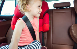 Portrait of happy little child girl sitting comfortable in car s Royalty Free Stock Photos