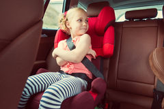 Portrait of happy little child girl sitting comfortable in car s royalty free stock photography