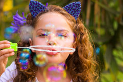 Portrait of a happy little curly girl playing with soap bubbles on a summer nature, wearing a blue ears of tiger Royalty Free Stock Images