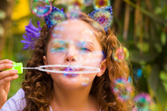 Portrait of a happy little curly girl playing with soap bubbles on a summer nature, wearing a blue ears of tiger Stock Images