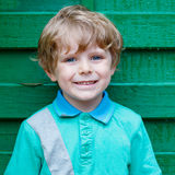 Portrait of happy little cute kid boy with blond hairs and blue Royalty Free Stock Photography