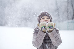 Portrait of a happy little girl on the background of a winter pa Royalty Free Stock Photos