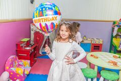 Portrait of happy little girl at birthday party holding balloon
