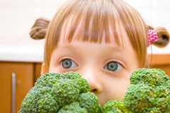 Portrait of a little girl with broccoli. Portrait of a happy little girl with broccoli at kitchen Royalty Free Stock Photography