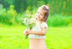 Portrait happy little girl child with bouquet flowers in spring Royalty Free Stock Photo