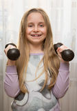 Portrait of happy little girl with dumbbells Royalty Free Stock Photos