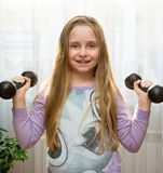 Portrait of happy little girl with dumbbells Stock Photos