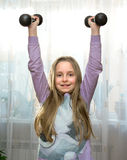 Portrait of happy little girl with dumbbells Stock Images
