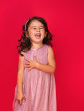 Portrait of a happy, little girl. Happy energetic little girl on red pointing fresh. Candid portrait of cheering beautiful young white Caucasian woman on red Royalty Free Stock Photo