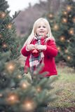 Portrait of happy little girl hanging bauble on tree outdoors stock photography