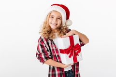 Portrait of a happy little girl holding gift box. And looking at camera isolated over white background Royalty Free Stock Image