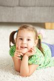 Portrait of happy little girl at home. Portrait of happy little girl lying on floor at home looking at camera, smiling royalty free stock photo