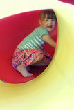 Portrait of happy little girl inside yellow plastic tube Royalty Free Stock Images