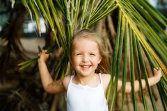 Portrait of happy little girl with palm leaf. Summer vacations concept, tropical vibes. Kid smiling. royalty free stock image