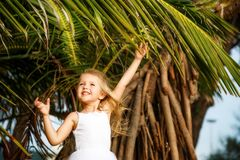 Portrait of happy little girl with palm leaf. Summer vacations concept, tropical vibes. Kid smiling. royalty free stock photo