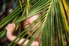 Portrait of happy little girl with palm leaf. Summer vacations concept, tropical vibes. Kid smiling. stock photos