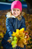 Portrait of happy little girl playing with maple leaves in autum Stock Image